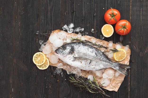 Rauwe dorada vis of goudbrasem op ijs met schijfjes citroen en rozemarijn op zwarte houten achtergrond, plat leggen, bovenaanzicht