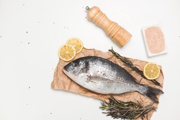 Rauwe dorada-vis of goudbrasem op papier over wit oppervlak, plat gelegd, bovenaanzicht