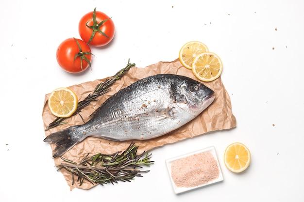 Rauwe dorada-vis of goudbrasem over wit oppervlak, plat gelegd, bovenaanzicht.
