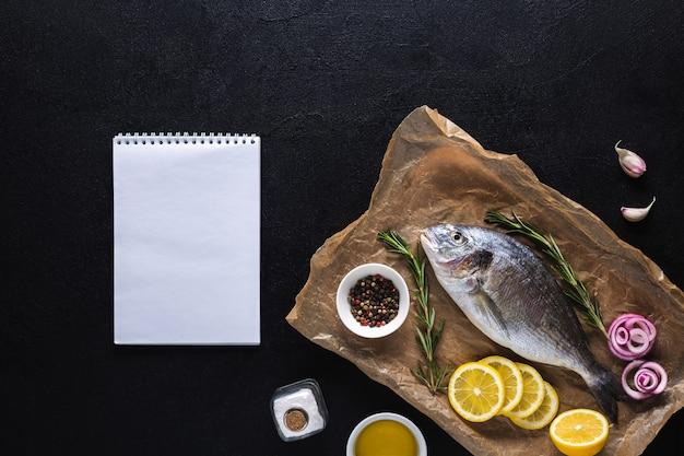 Rauwe dorado op kookpapier met een notitieboekje voor recept bovenaanzicht op een zwarte achtergrond