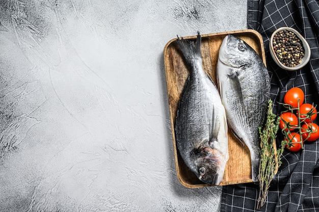Rauwe dorado-vis met kookingrediënten, kerstomaatjes, tijm, peper. grijze achtergrond