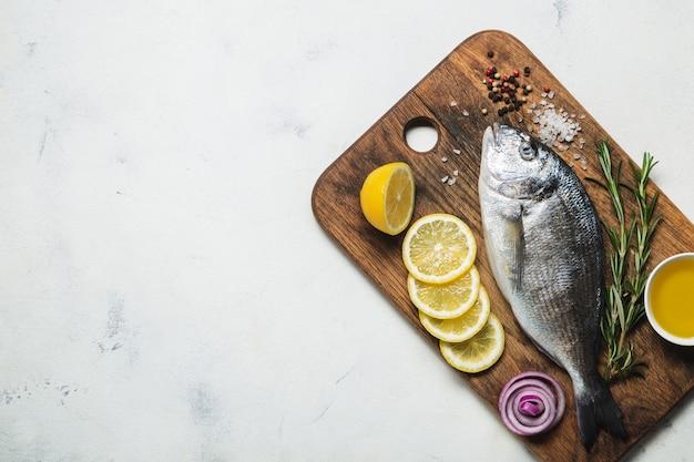 Rauwe dorado-vis op een houten snijplank bovenaanzicht op een witte achtergrond ruimte kopiëren