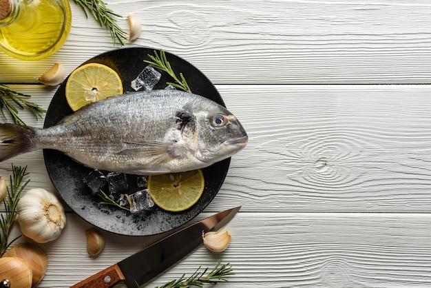 Rauwe dorado vis op een schotel en ingrediënten voor de bereiding.