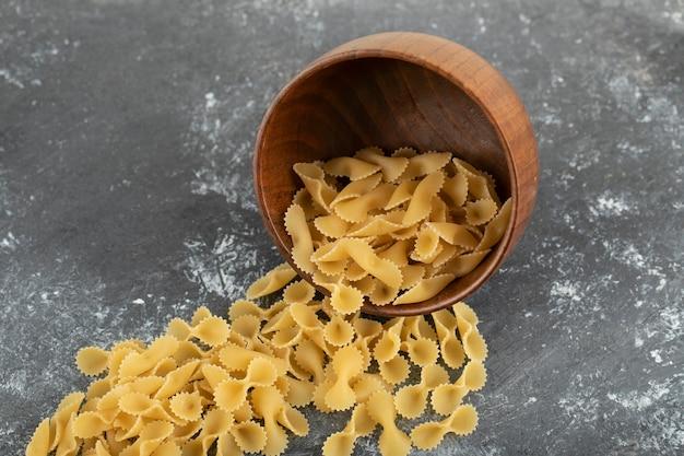 Rauwe droge farfalle tonde macaroni op een marmeren tafel.
