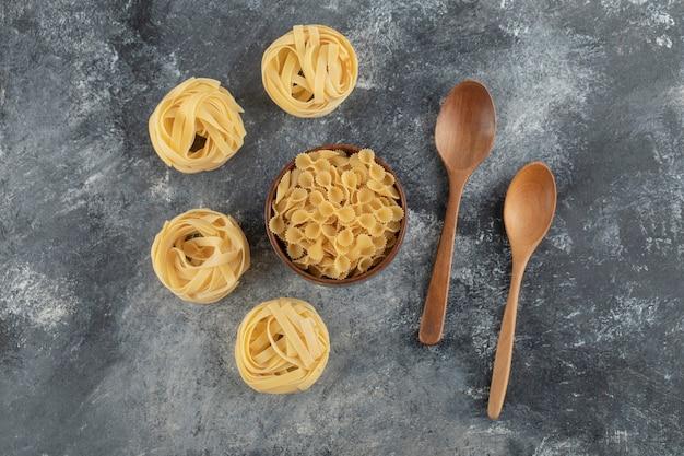Rauwe droge nestnoedels met farfalle tonde pasta op een marmeren tafel.