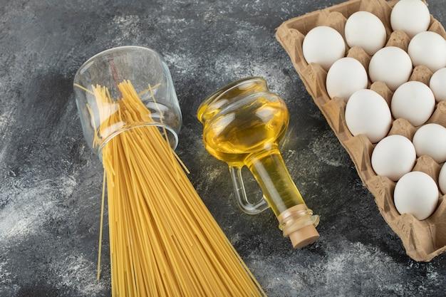 Rauwe droge spaghetti met ongekookte eieren en een fles olie.