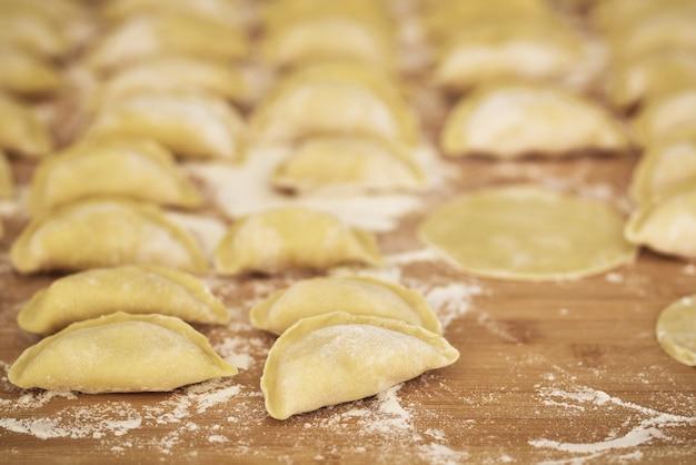 Rauwe dumplings op een houten bord het proces van het maken van dumplings