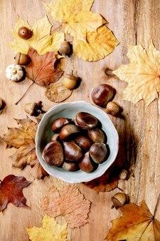 Rauwe eetbare kastanjes in keramische kom en gele herfst esdoorn bladeren over houten tafel. plat leggen