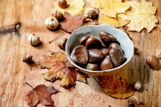Rauwe eetbare kastanjes in keramische kom en gele herfst esdoorn bladeren over houten tafel