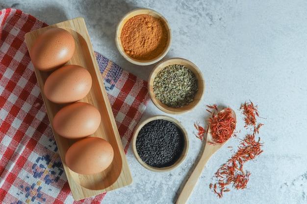Rauwe eieren en verschillende kruiden op stenen achtergrond.