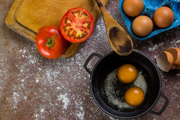 Rauwe eieren in pan of pot vergezeld van tomaat en verse eieren op snijplank en houten lepel