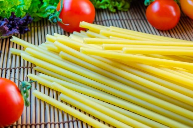 Rauwe en lange pasta en groenten op tafel
