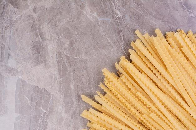 Rauwe en ongekookte pasta's geïsoleerd op het marmeren oppervlak