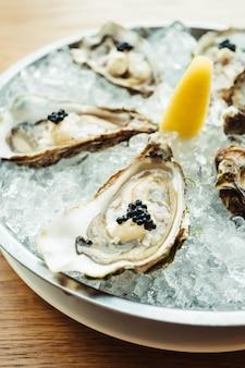 Rauwe en verse oester met kaviaar bovenop en citroen