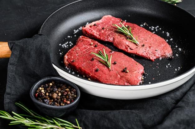 Rauwe entrecote in een koekenpan. rund vlees. zwarte achtergrond. bovenaanzicht
