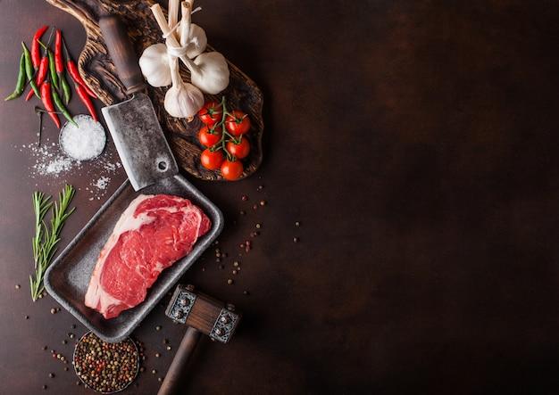 Rauwe entrecote in plastic bakje met peper en zout en vintage vleesbijlen en hamer