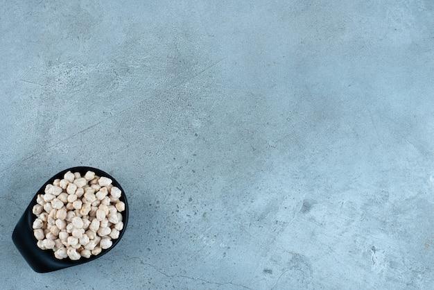 Rauwe erwtenbonen in een zwarte kop op blauwe achtergrond. hoge kwaliteit foto
