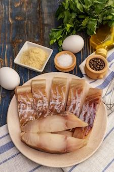 Rauwe filet van koolvis en frituur ingrediënten. verse plakjes op een bord, kruiden, eieren, olie, paneermeel, peterselie