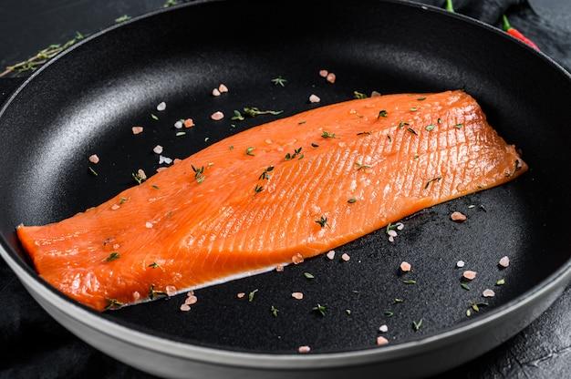 Rauwe forelfilet met zout en spaanse peper in een pan. biologische vis. zwart oppervlak. bovenaanzicht.