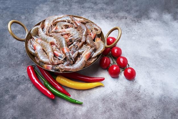 Rauwe garnalen op een vintage schotel op het grijze achtergrond gezonde zeevruchten concept