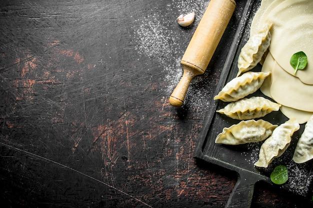 Rauwe gedza-knoedel. het deeg voor de bereiding van dumplings gedza op donkere houten tafel