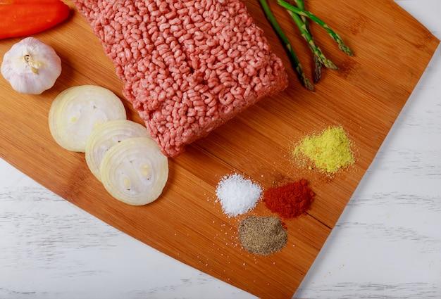 Rauwe gehakt ingrediënten op peper met ui, kruiden en asperges