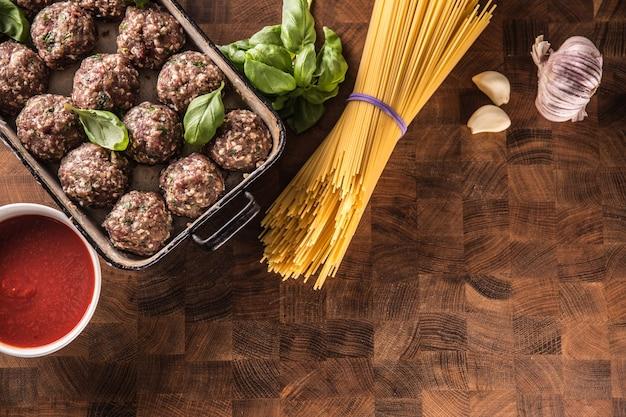 Rauwe gehaktballen basilicum tomatensaus knoflook en spaghetti op slager bord.