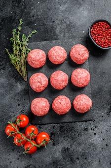 Rauwe gehaktballen, gehakt varkensvlees. zwarte achtergrond. bovenaanzicht