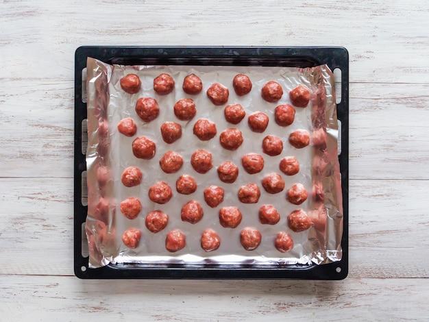 Rauwe gehaktballen van gehakt op een bakplaat.