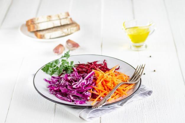 Rauwe gehakte groenten paarse kool, bieten, wortelen en peterselie greens met olijfolie, op een witte plaat.