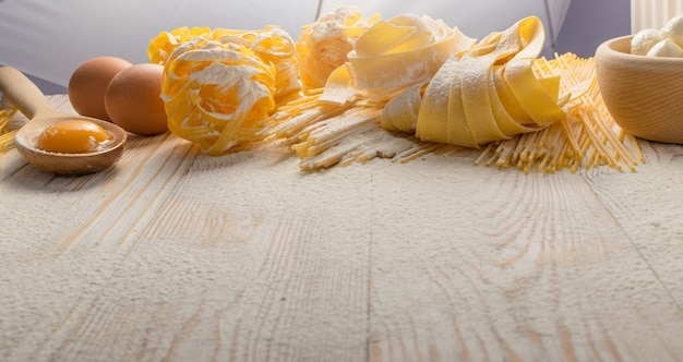 Rauwe gele italiaanse pasta pappardelle, fettuccine of tagliatelle close-up met eieren. ei zelfgemaakte noedels kookproces met lange macaroni of spaghetti