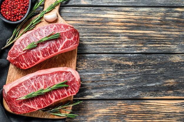 Rauwe gemarmerde biefstuk, top mes vlees steak op zwart. bovenaanzicht. kopieer ruimte.