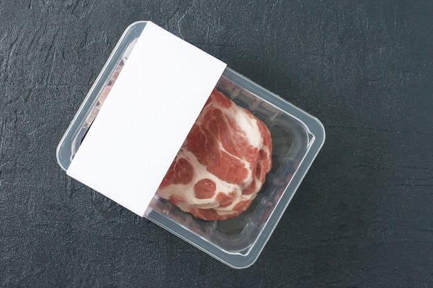 Rauwe gemarmerde varkenssteak in vacuümverpakking op zwarte achtergrond, bovenaanzicht, logomodel voor ontwerp