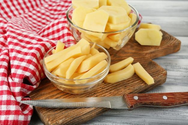 Rauwe geschilde en gesneden aardappelen in glazen kommen, op snijplank, op een houten achtergrond kleur