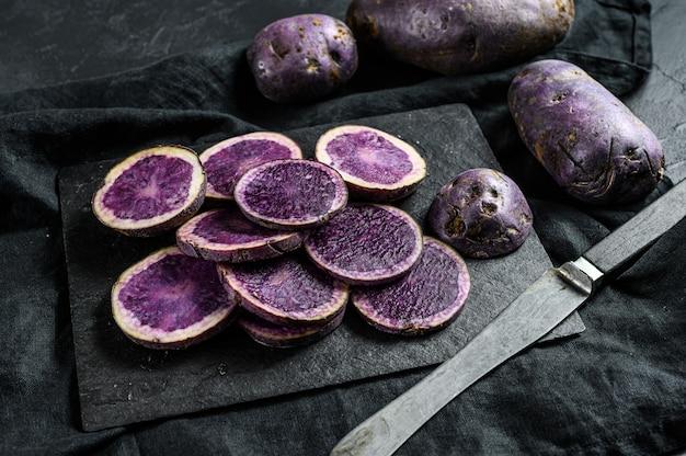 Rauwe gesneden paarse aardappelen.