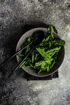 Rauwe gezonde salade met verse rucola bladeren geserveerd in een kom op betonnen tafel