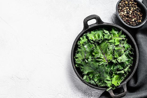 Rauwe groene boerenkoolsalade in een pan. biologische vegetarische gerechten. witte achtergrond. bovenaanzicht. kopieer ruimte.