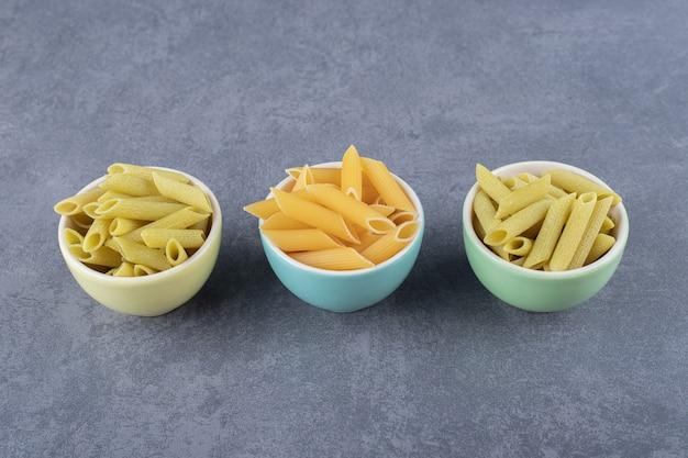 Rauwe groene en gele penne pasta in kleurrijke kommen. Gratis Foto