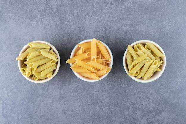 Rauwe groene en gele penne pasta in kleurrijke kommen.