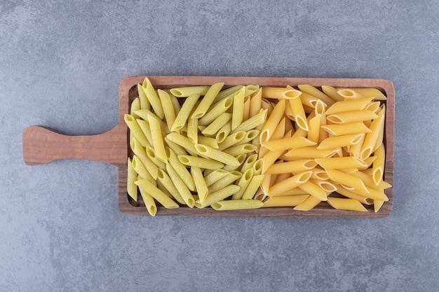 Rauwe groene en gele penne pasta op een houten bord.