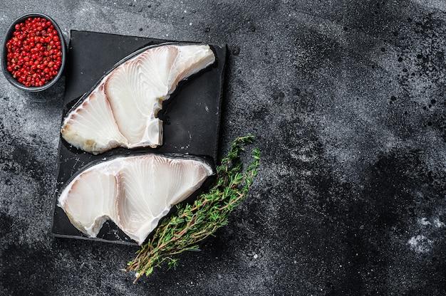 Rauwe haai vis steaks op een bord op zwarte tafel. bovenaanzicht.