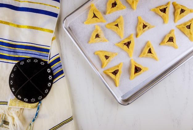 Rauwe hamantaschen koekjes op bakplaat met kippa en tallit.