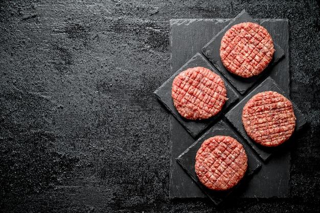 Rauwe hamburgers op zwarte stenen stands. op rustieke ondergrond