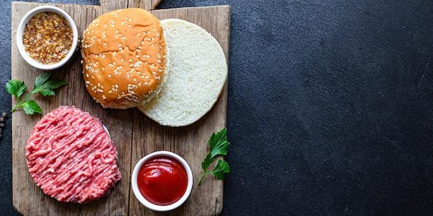 Rauwe hamburgerset kotelet vlees, rol, saus en meer