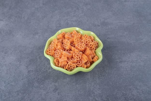Rauwe hartvormige pasta in groene kom.