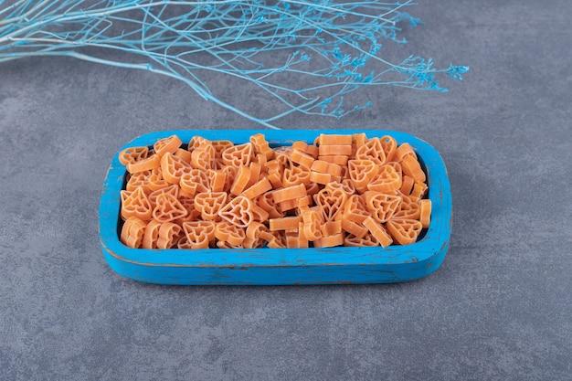 Rauwe hartvormige pasta op blauw bord.