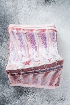 Rauwe hele rek van varkenslende met ribben op keukentafel. witte achtergrond. bovenaanzicht.