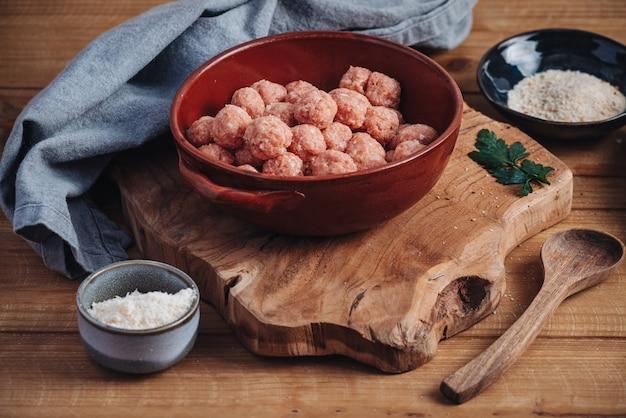 Rauwe huisgemaakte italiaanse traditionele gehaktballen met parmezaanse kaas en brood