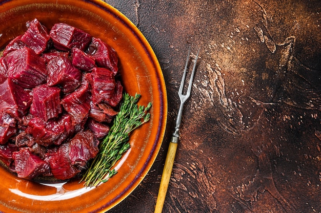 Rauwe in blokjes gesneden biefstuk van het elandvlees voor een goulash op een bord. donkere achtergrond.