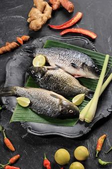 Rauwe ingrediënten van pesmol ikan mas gold fish met gele kerriekruiden sjalotten limoenblad